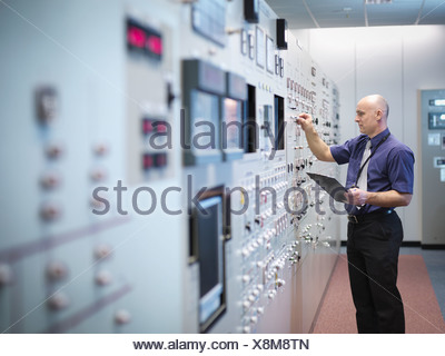 Engineer inspecting nuclear power station control room simulator - Stock Photo