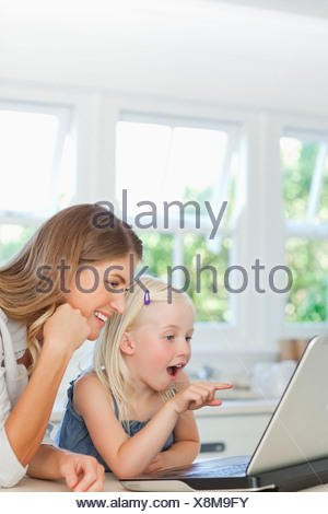 Surprised girl looks at the laptop with her smiling mother - Stock Photo
