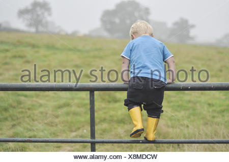 Boy climbing metal fence - Stock Photo