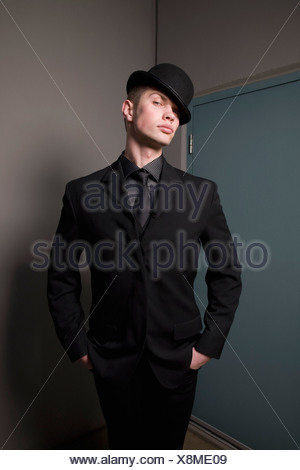 Man in business suit and bowler hat - Stock Photo