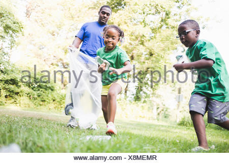 Father picking up litter with son and daughter at parkland eco camp