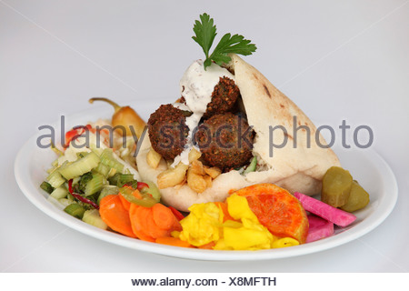 Falafel in pita bread with salad and tahini sauce and pickles - Stock Photo