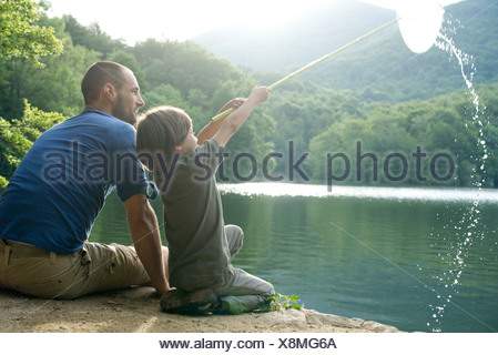 Father and son fishing, boy holding up fishing net - Stock Photo