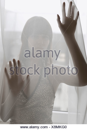 Woman standing behind a transparent curtain - Stock Photo