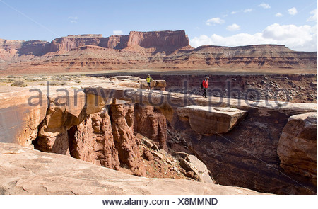 Two hikers wander onto the flat Musselman Arch along the White Rim Road canyonlands national Park, Utah - Stock Photo