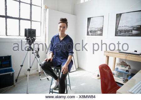 Portrait confident female photographer sitting on stool in art studio - Stock Photo
