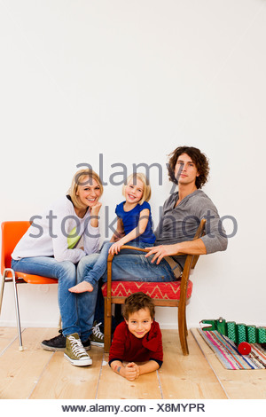 Studio portrait of couple sitting with son and daughter - Stock Photo