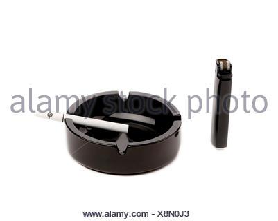 Black ceramic ashtray with cigarette and lighter. - Stock Photo