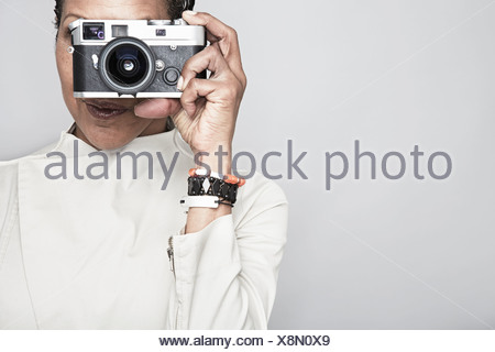 Studio portrait of mature woman holding up camera - Stock Photo