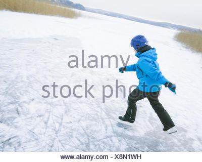 Boy (10-11) ice-skating on surface of frozen lake - Stock Photo