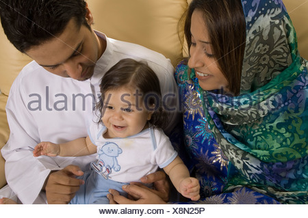 Family of three sitting in the living room - Stock Photo