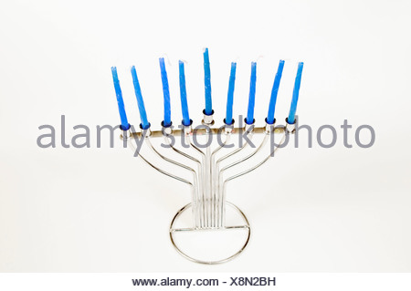 Silver Hannukah Menorah with blue candles on white background - Stock Photo