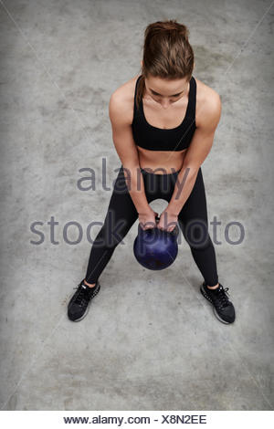 overhead view of muscular young woman lying on exercise