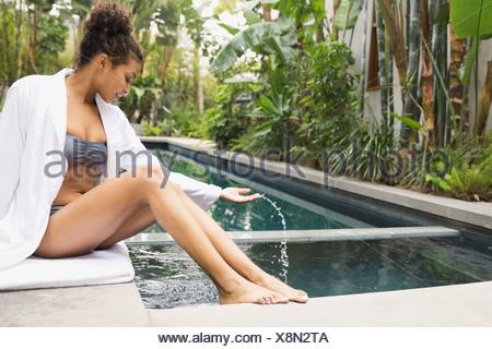 Woman sitting near hot tub at day spa - Stock Photo