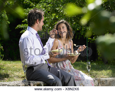 Wedding guests feeding each other cake - Stock Photo