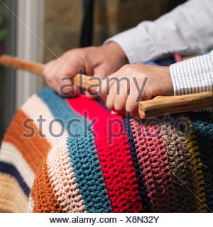Seated older man holding cane - Stock Photo