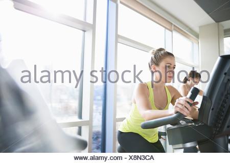 Women exercising on stationary bikes in fitness center - Stock Photo