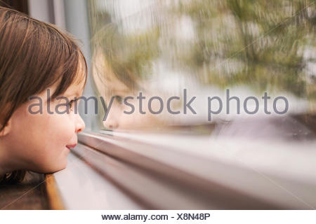 Girl on a train looking out of the window - Stock Photo