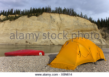 Camp, tent and canoe on a gravel bar, high cut bank, river cliff, erosion, behind, upper Liard River, Yukon Territory, Canada - Stock Photo