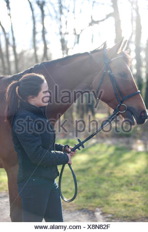 A young woman leading a Thoroughbred horse in hand - Stock Photo