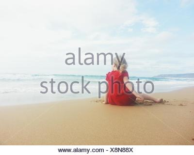 Girl sitting on the beach - Stock Photo