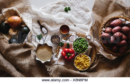Various Vegetables, including red potatoes, spring peas, corn, avocados, onions, and garlic are displayed on a white farm style - Stock Photo