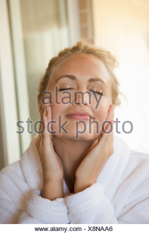 Woman rubbing moisturizer on face - Stock Photo