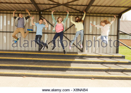 Five boys and girls jumping mid air in stadium stand - Stock Photo