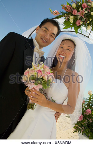 Bride and Groom under archway, (portrait) - Stock Photo