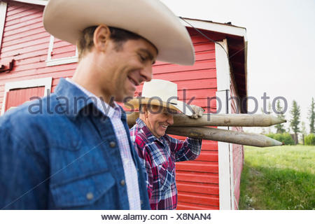 Ranchers carrying fence posts outside barn - Stock Photo