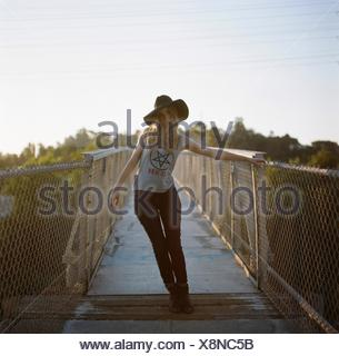 Full Length Portrait Of Fashionable Young Woman Standing On Footbridge - Stock Photo