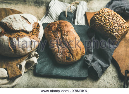 Various bread selection. Rye, wheat and multigrain rustic bread loaves on kitchen towels and wooden boards over grey concrete stone background - Stock Photo