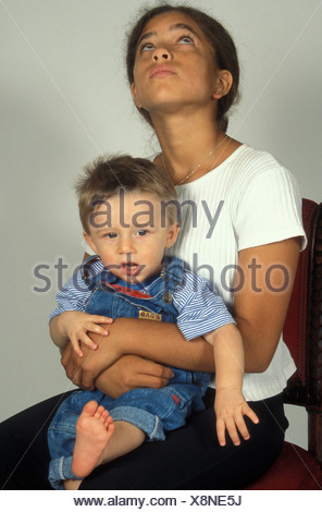 annoyed young girl holding baby boy - Stock Photo