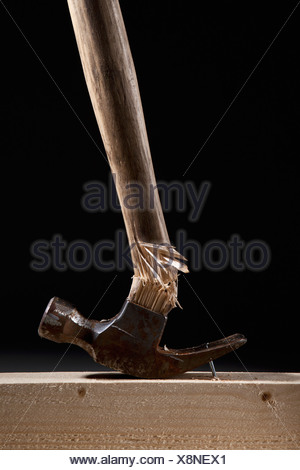 A hammer handle breaking while trying to remove a nail from a beam - Stock Photo