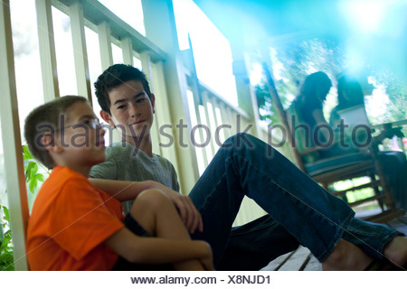 Two young boys sitting on porch - Stock Photo