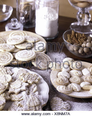 A variety of biscuits dusted with icimg sugar on white plates - Stock Photo