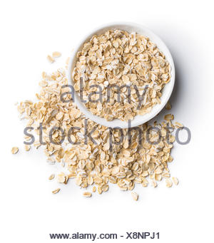Dry rolled oatmeal in bowl. - Stock Photo