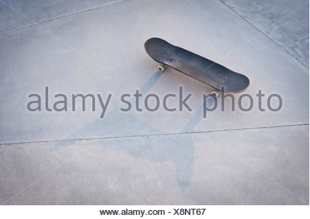 Belgium, Mechelen, Skateboard lying on ground in public skatepark - Stock Photo