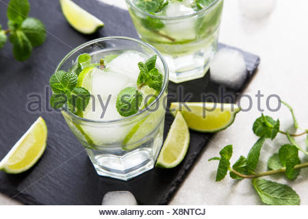 Cold refreshing summer lemonade mojito in a glass on a slate board and stone background. - Stock Photo