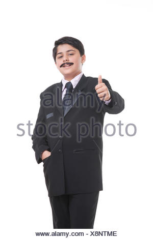Portrait of boy dressed as businessman giving thumbs up Stock Photo