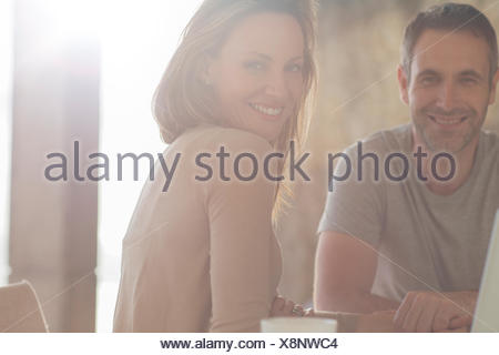 Couple smiling at breakfast table - Stock Photo