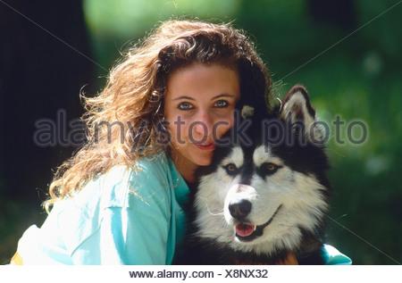 woman embracing Siberian Husky. - Stock Photo