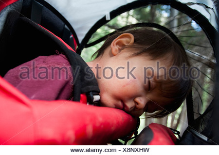 14 month old boy sleeps in backpack carried by mother, backpacking in Maroon Bells Snowmass Wilderness outside Aspen, Colorado - Stock Photo