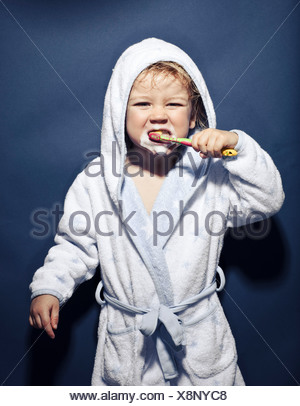 Young girl with frothy mouth brushing teeth - Stock Photo