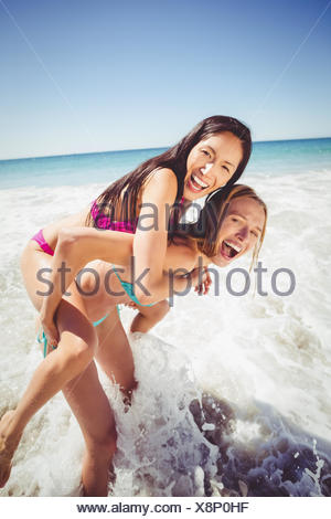Woman giving piggy back to her female friend - Stock Photo