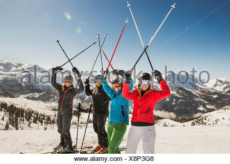 Portrait of skiers on slope, holding ski poles in the air - Stock Photo