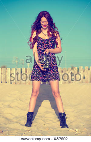 Spain, El Puerto de Santa Maria, smiling young woman using old film camera on the beach - Stock Photo