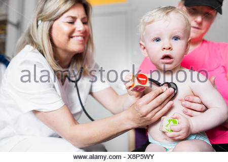 Baby (6-11 months) being examined by doctor - Stock Photo