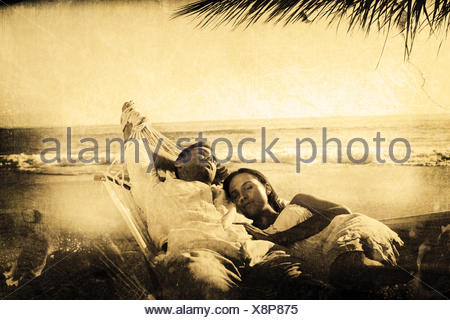 Composite image of calm couple napping in a hammock - Stock Photo