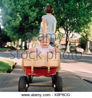 A mother pulling her young son in a wagon, focus on boy - Stock Photo